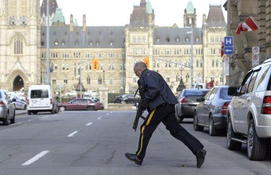 Photo: Adrian Wyld La Presse canadienne Un policier prend position devant le parlement où des coups de feu ont été échangés.