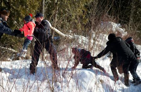 Royal Canadian Mounted Police (RCMP) officers assist a child from a family that claimed to be from Sudan as they walk across the U.S.-Canada border into Hemmingford, Canada, from Champlain in New York. REUTERS/Christinne Muschi